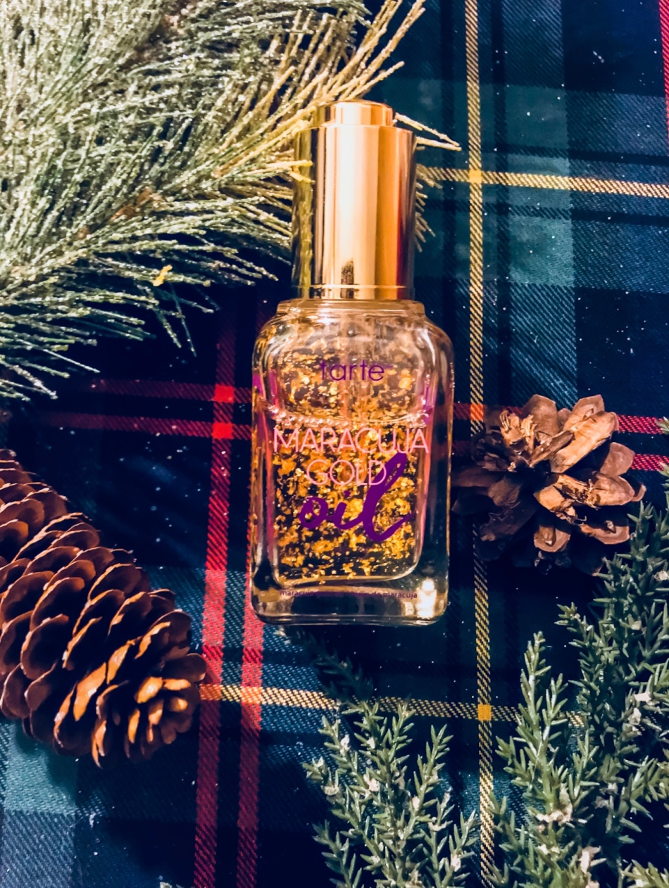 Glass bottle of Maracuja Gold oil on a green plaid background with frosted pine branches and pine cones scattered around it.